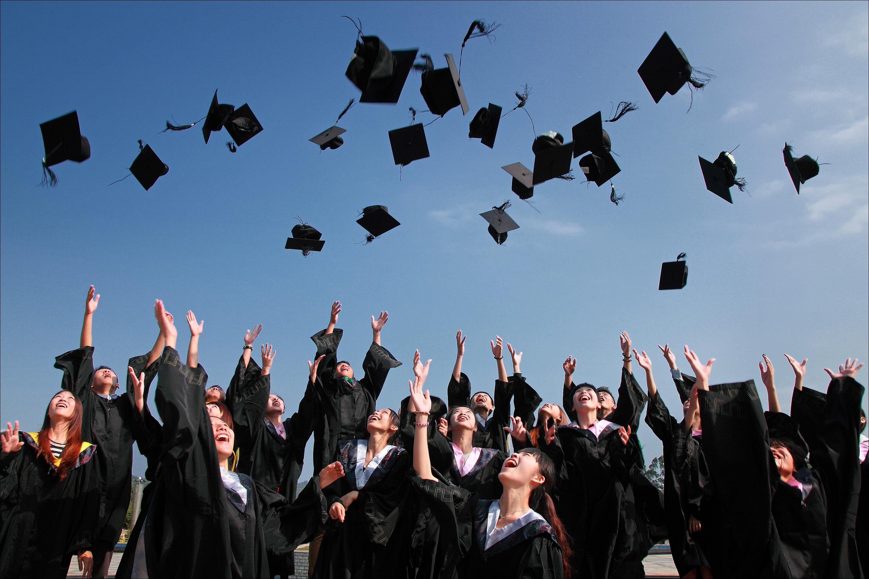 Graduating students throwing their caps in the air
